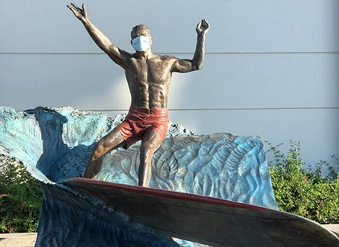 Famous Hermosa Beach Surfer statue wears a mask